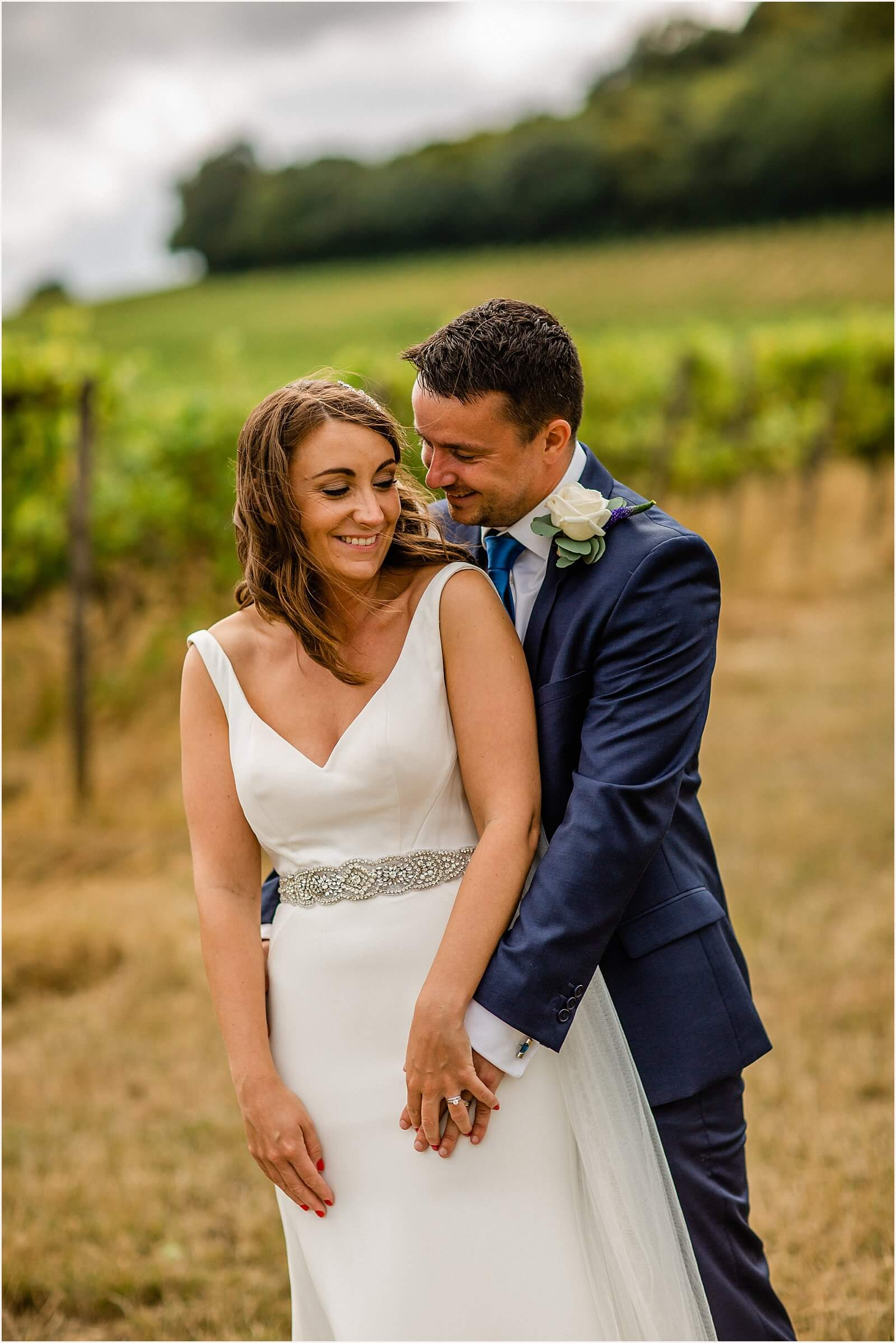 bride and groom holding each other in denbies vineyard wedding