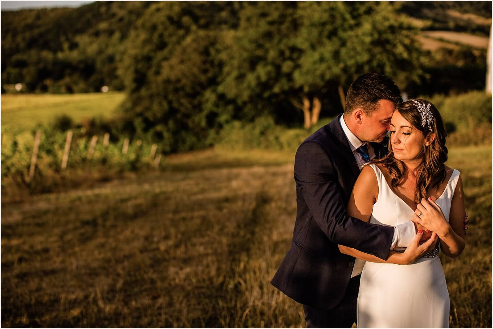 bride and groom holding each other aoutside the vineyard at their Denbies Vineyard Wedding