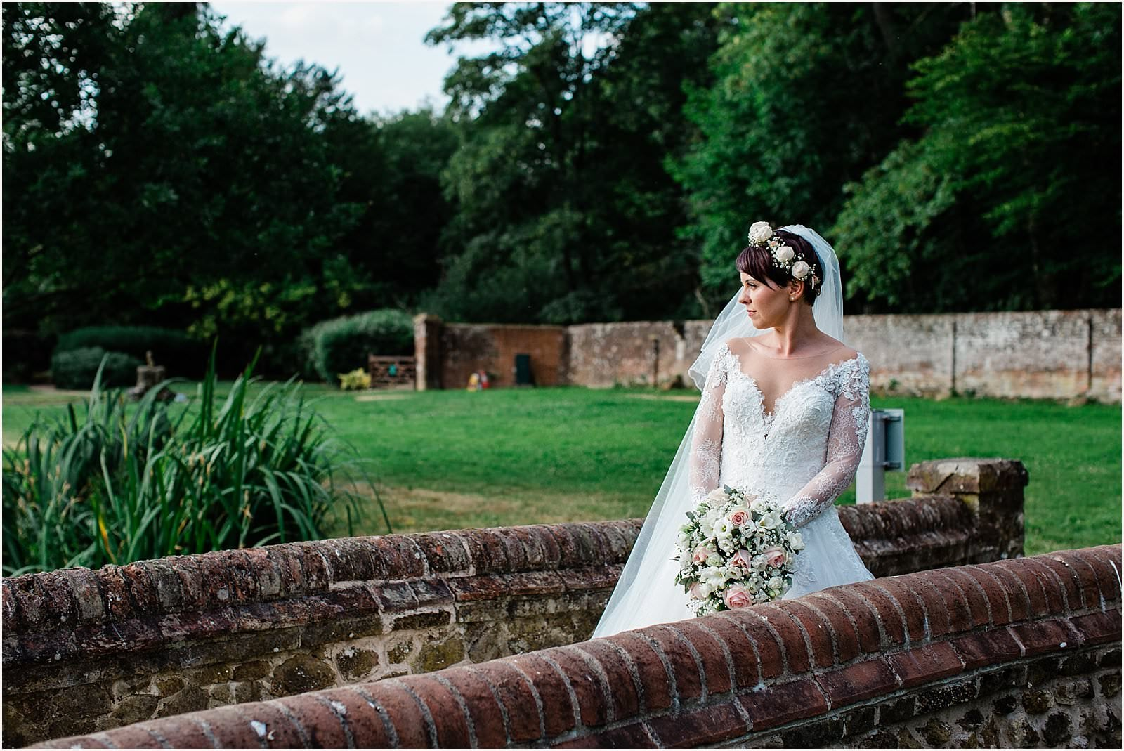Bride looking over her shoulder at her wotton house wedding