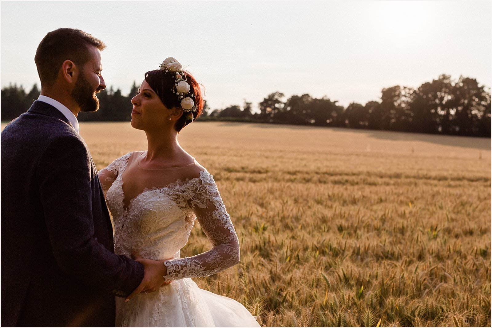 bride and groom gazing into each others eyes in a wheat field in wotton house wedding