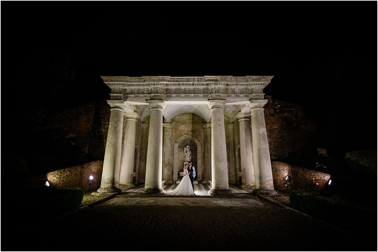 bride and groom under roman temple at night in wotton house