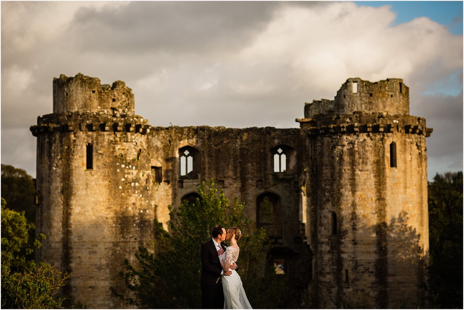 bride and groom kissing in front of a castle
