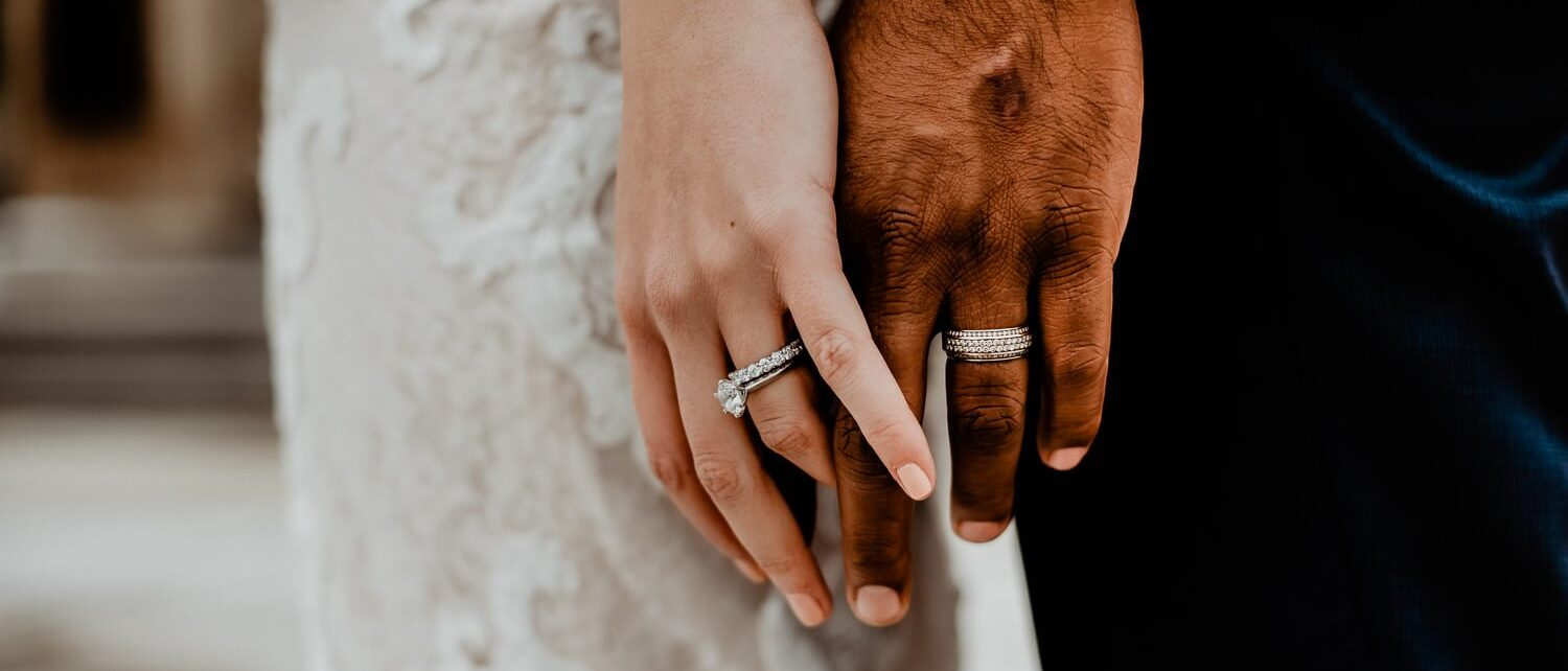 newly weds holding hands with wedding rings